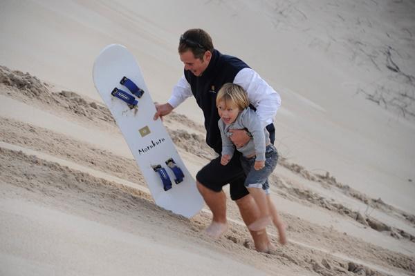 Sandboarding in the dunes at Morukuru Ocean House